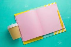 Schein- oben offener Notizblock mit dem leeren rosa Papier-sheetscoffee, zu gehen Schale ein vibrierender blauer Hintergrund stockbild