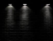 Scheinwerfer auf einer schwarzen Backsteinmauer Stockbilder