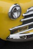 Scheinwerfer und Grill des hellen gelben Weinlese Chevy Automobils Stockfotos