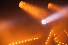 Scheinwerferlichter mit gelben Strahlen im Rauche stockbild
