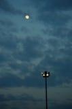 Scheinwerferlichtpfosten und der Mond Stockbild