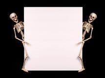Scheletri che tengono spazio in bianco vuoto sopra il nero Halloween Fotografia Stock Libera da Diritti