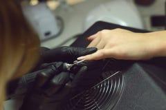 Schellackborttagning Förlagen gör en manikyr Avslappnande dag på skönhetsalongen Manikyristförlagen gör manikyr på handen för kvi fotografering för bildbyråer
