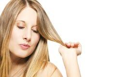 Schelmisch blonde Frau, die mit ihren Haaren spielt Stockfotos