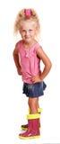 Schelmisches kleines blondes Mädchen in der Bluse, Rock, Gummistiefel lokalisiert Stockfoto
