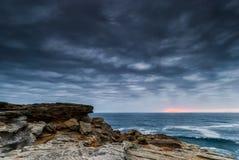 Schemeringzeegezicht met rotsen Stock Foto