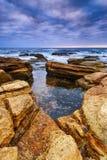 Schemeringzeegezicht met rotsen Stock Foto's
