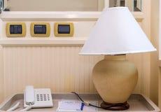 schemerlamp met telefoon op het bed in ruimte Stock Foto