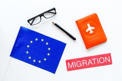 Schengen visa. Immigration to Europe concept. Text immigration near passport cover and european flag on white background. Top view stock image