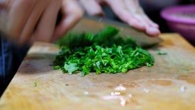 Schenk de Spaanse peper aan de mand in het kitchenchopping van koriander op scherpe raad in die ingrediënt voor het koken voorber stock videobeelden