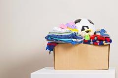 Schenkingsvakje met speelgoed, boeken, die zich voor liefdadigheid kleden stock afbeeldingen