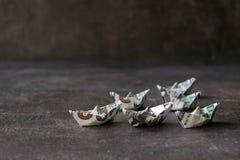 Schepen van geld op een geweven donkere achtergrond Vele Origamischepen stock foto's