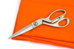 Scheren auf orange Stoff Lizenzfreies Stockbild