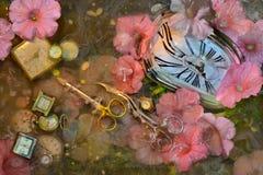 Scheren: ein fantastisches Stillleben mit gebogenen Scheren, Skala von Uhren und rosa Blumen im Wasser mit Farbenscheidungen, ein Lizenzfreie Stockfotografie