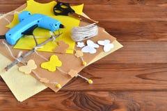 Scheren, Heißklebepistole, Blätter des Filzes, dekorativer Anhänger mit Filzschmetterlingen und Blumen Hölzerner Hintergrund mit  Lizenzfreies Stockbild