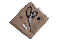 Scheren, Knopf, Spule des Threads und eine Nadel auf Sackleinen Stockfotos