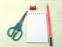 Scheren, Notizbuch, Bleistift und Bleistiftspitzer Lizenzfreie Stockfotos