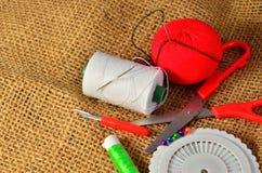 Scheren, Spulen mit Thread und Nadeln auf dem alten Gewebe Stockfotografie