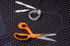 Scheren stellen her und bewegen, Zentimeterband auf einem Hintergrund von Blauem Schritt für Schritt fort Lizenzfreie Stockbilder