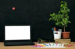 Scheren und Bleistifte auf dem Hintergrund des Kraftpapiers Zurück zu Schule-Konzept Laptop mit leerem Bildschirm auf dem Tisch Stockfoto