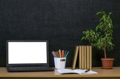 Scheren und Bleistifte auf dem Hintergrund des Kraftpapiers Zurück zu Schule-Konzept Laptop mit leerem Bildschirm auf dem Tisch Lizenzfreie Stockfotografie