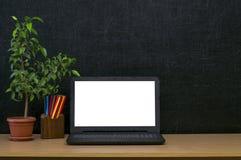 Scheren und Bleistifte auf dem Hintergrund des Kraftpapiers Zurück zu Schule-Konzept Laptop mit leerem Bildschirm auf dem Tisch Lizenzfreie Stockbilder