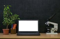 Scheren und Bleistifte auf dem Hintergrund des Kraftpapiers Zurück zu Schule-Konzept Laptop mit leerem Bildschirm auf dem Tisch Stockbild