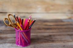 Scheren und bunte Bleistifte von violettem gelbem rosarotem und orange in der stationären Schale auf Holztisch und Hintergrund Lizenzfreie Stockfotos