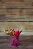 Scheren und bunte Bleistifte von violettem gelbem rosarotem und orange in der stationären Schale auf Holztisch und Hintergrund Stockfotos