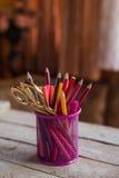 Scheren und bunte Bleistifte von violettem gelbem rosarotem und orange in der stationären Schale auf Holztisch und Hintergrund Stockfoto
