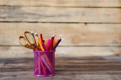 Scheren und bunte Bleistifte von violettem gelbem rosarotem und orange in der stationären Schale auf Holztisch und Hintergrund Co Stockfotos