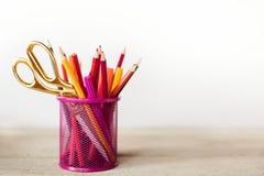 Scheren und bunte Bleistifte von violettem gelbem rosarotem und orange in der stationären Schale auf Holztisch- und Weißhintergru Stockfotos