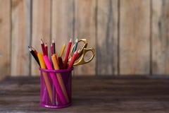 Scheren und bunte Bleistifte von violettem gelbem rosarotem und orange in der stationären Schale auf Holztisch- und Weißhintergru Stockbilder