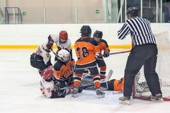 Schermaglia al portone nel hockey su ghiaccio dei bambini Immagini Stock