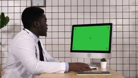 In schermo afroamericano del dottore Looking At Computer del laboratorio medico Visualizzazione bianca stock footage
