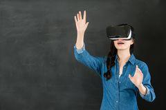 Schermo asiatico di controllo della studentessa con la cuffia avricolare di VR Fotografie Stock Libere da Diritti