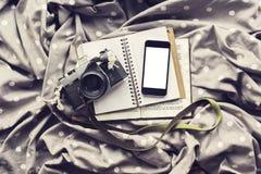 Schermo bianco in bianco dello smartphone con la macchina fotografica ed il diario di vecchio stile immagini stock