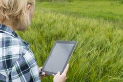 Schermo in bianco del computer della compressa di signora nel campo verde Fotografie Stock