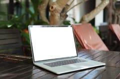 Schermo bianco del computer portatile sul fondo di visualizzazione della località di soggiorno della tavola immagine stock