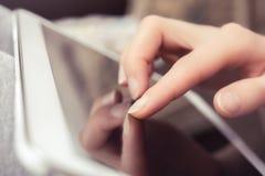 Schermo in bianco di una compressa di affari commovente da un dito femminile Fotografie Stock Libere da Diritti