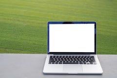 Schermo in bianco sul computer portatile con il fondo di struttura dell'erba verde, libero Fotografia Stock