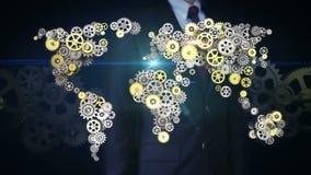 Schermo commovente dell'uomo d'affari, ingranaggi dorati d'acciaio che fanno la mappa di mondo globale globale colleghi la tecnol video d archivio