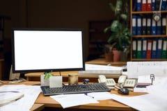 Schermo del ritaglio del monitor del computer sullo scrittorio alla notte, costruente con i disegni Immagine Stock
