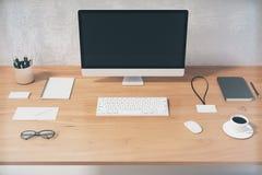 Schermo di computer nero in bianco con gli accessori dell'ufficio sui tum di legno Immagini Stock