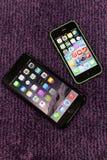 schermo domestico più di iphone 6 in pieno delle icone con un iphone 5c parallelamente Fotografia Stock
