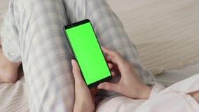 Schermo verde sul telefono cellulare della giovane donna a letto a casa per la chiave di intensità video d archivio
