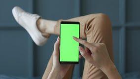 Schermo verde sul telefono cellulare della stanza della giovane donna a letto a casa per la chiave di intensità video d archivio