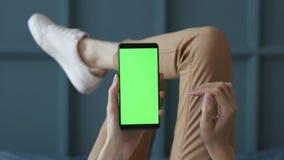 Schermo verde sul telefono cellulare della stanza della giovane donna a letto a casa per la chiave di intensit? stock footage