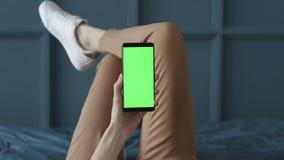 Schermo verde sul telefono cellulare della stanza della giovane donna a letto a casa per la chiave di intensit? video d archivio