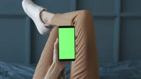 Schermo verde sul telefono cellulare della stanza della giovane donna a letto a casa per la chiave di intensit? archivi video